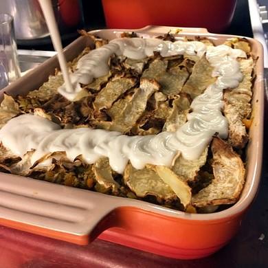 vegansk bechamelsås hälls på glutenfri lasagne med rotselleri